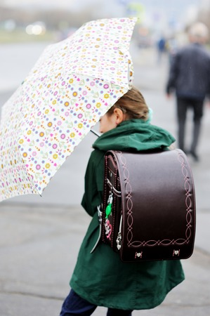 school aged: Adorable, elegant school aged kid  girl ,holding colorful umbrella walking in the city street in rainy day Stock Photo