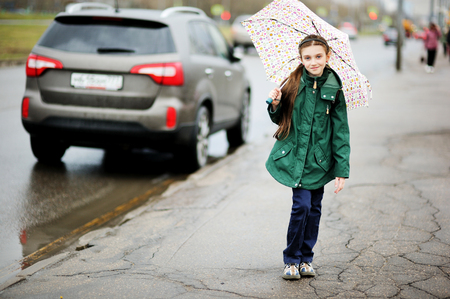 street kid: Adorable, elegant school aged kid  girl ,holding colorful umbrella walking in the city street in rainy day Stock Photo