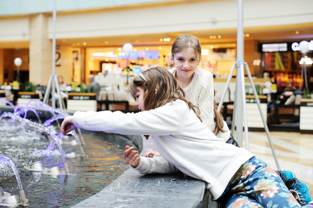 playing the market: Two cute little girls playing with a city fountain on the market street Stock Photo