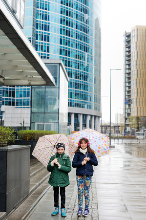 10 years girls: Cute 10 years old girls in light fashion jackets walking outdoors with umbrellas at rainy city Stock Photo