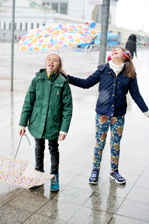 10 years girls: Cute 10 years old girls in light fashion jackets catching rain drops walking outdoors with umbrellas at rainy city