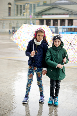 schooler: Cute 10 years old girls in light fashion jackets walking outdoors with umbrellas at rainy city Stock Photo