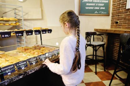 bakery store: Little girl choosing bread in a food bakery store