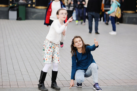 children at school: Two adorable girls walking and having fun on the spring city streets. Moscow. Russia