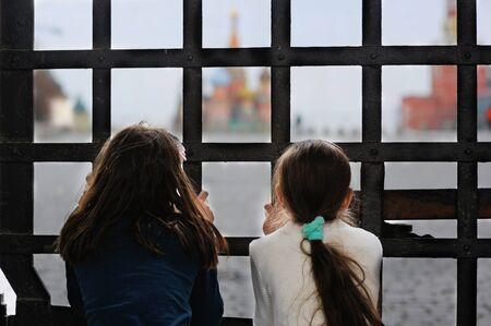 portones: Dos chicas adorables que buscan en el cuadrado rojo de las puertas cerradas. Moscú. Rusia