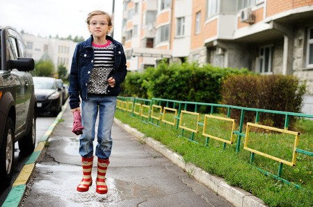 Adorable, elegant school aged kid  girl ,holding colorful umbrella walking in the city street in rainy day photo