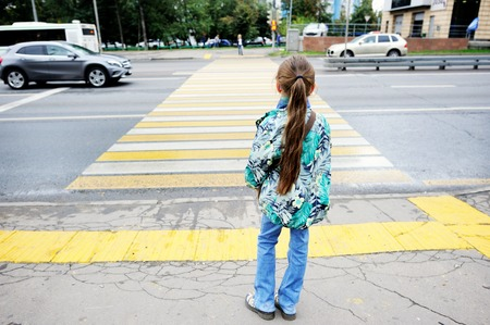 Adorableschool aged kid girl in glasses and fashion  clothes standing  near the pedestrian crossing on the city street