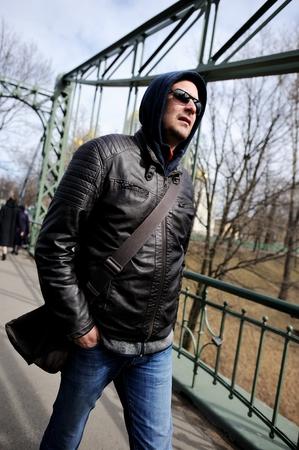 jacket: el hombre de moda urbana caminando a través del puente