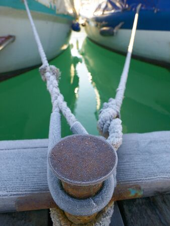 bollard: Bollard with two ropes from yachts Stock Photo