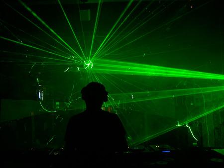 DJ mixen van muziek tegen lasershow