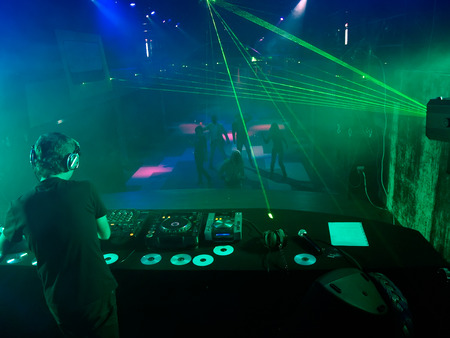 dancefloor: DJ mixing music in nightclub