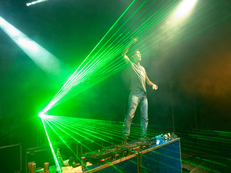 upraised: DJ with upraised arm standing on the table near the music control panel in the green laser rays