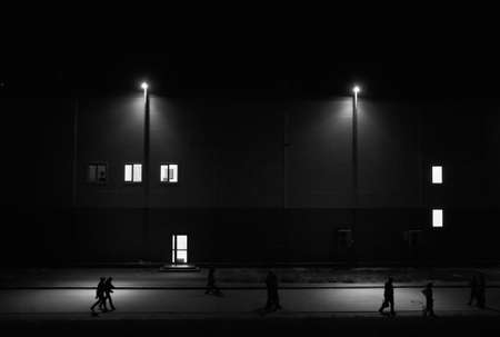 streetlights: People walking on the night street with streetlights against the building with luminous windows