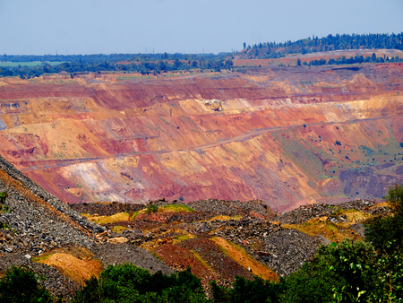 open cast mine: Open cast mine with natural landscape on the background and colorful ore dump on the foreground Stock Photo