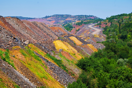 dumps: Outside the open cast mine with trees beside colorful depleted iron ore dumps and road on the background Stock Photo