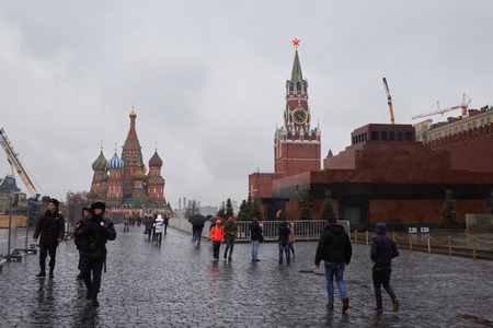 spasskaya: Tourists and police walk at Red Square along the Lenins Mausoleum, Spasskaya tower and Saint Basils Cathedral Editorial