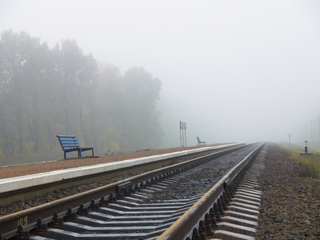railroad station platform: Two blue benches on the empty railroad station platform on foggy day