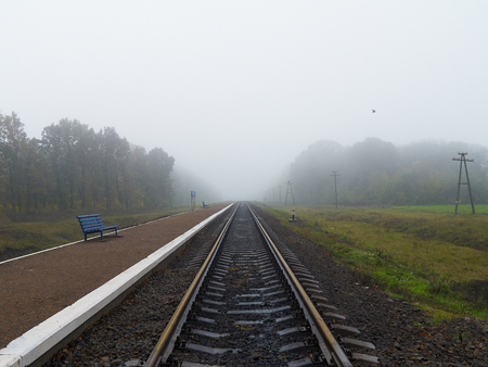 railroad station platform: Empty railroad station platform with two benches on foggy day