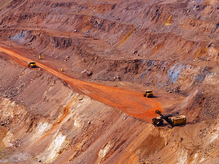 dragline: Top view of terraced open-pit mine with quarry excavator loading iron ore to dump truck Stock Photo