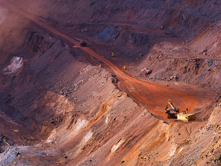 dragline: Top view of sunlit open-pit mine with quarry excavator loading iron ore to dump truck