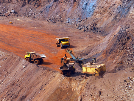 dragline: Quarry excavator load the iron ore to big dump truck in openpit mine with another two trucks waiting in queue