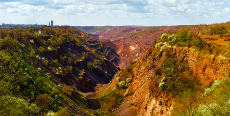 dragline: Panoramic view to extended colorful open-pit mine with drawn hills in the foreground