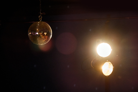 golden ball: Golden mirror ball highlighted with two spotlights shining in the darkness