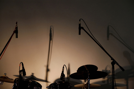 without people: Empty stage with silhouettes and shadows of microphones on stands and drum set