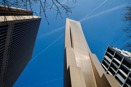Frankfurt am Main, Germany - March 16, 2017: Lower view of modernist building sculpture next to Frankfurter Büro Center (Frankfurt Office Centre) on Mainzer Landstraße against the blue sky with contrails.