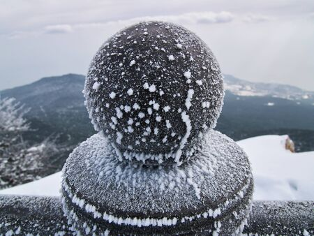 Wide angle view of iron ball on the top of column accreted with big pieces of frost against the snow-cowered hill and somber sky with clouds Stock Photo