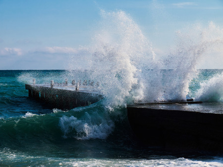 Big teal wave splashing out centre of empty stone pier with bollards on sunny winter day Stock Photo