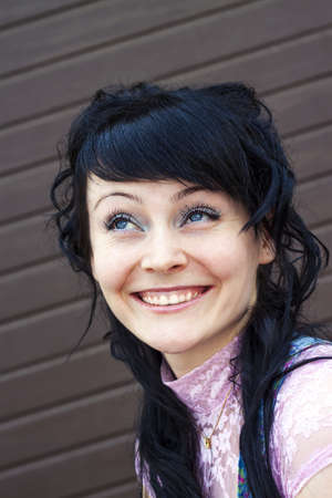 The young attractive woman with blue eyes smiling happily, there appear mimic wrinkles on the face