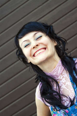 The young attractive woman with closed eyes smiling happily, there appear mimic wrinkles on the face