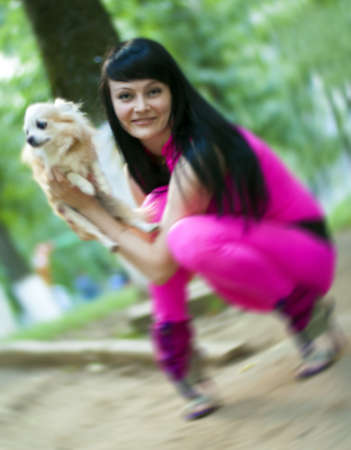 Attractive young woman with cream color lapdog  Motion blur without focus