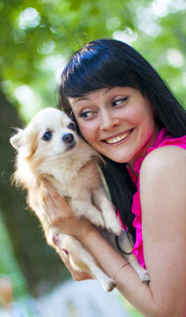 Attractive young woman with cream color lapdog