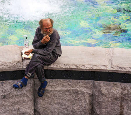 MOSCOW, RUSSIA 25 AUGUST 2012  Homeless old man drink vodka on the fountain in the summer at the center of Moscow  Stock Photo - 15080519