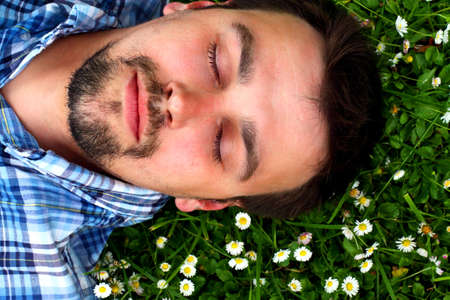 Young man lying on grass with flowers