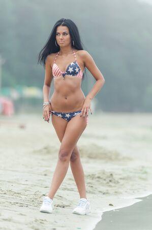 Mädchen am Strand mit amerikanischer Flagge Standard-Bild - 83599534