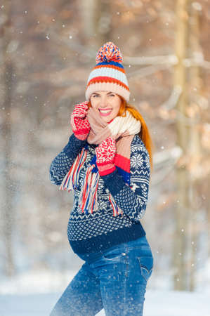 Beautiful pregnant woman in winter forest