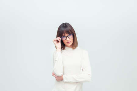 Portrait of beautiful young woman in eyeglasses on white background