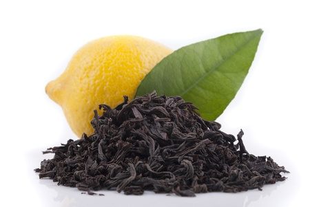 Black tea, lemon and green leaf on a white background