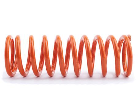 elasticidad: Resorte del metal rojo en un fondo blanco. Foto de archivo