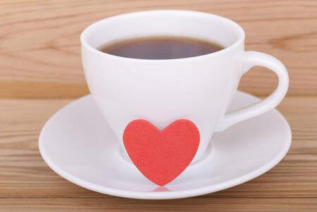 Cup of coffee and heart on wooden background  photo