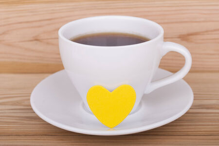 Cup of coffee and heart on wooden background. photo
