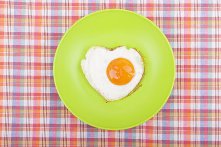 Scrambled in a heart shape on a plate. photo