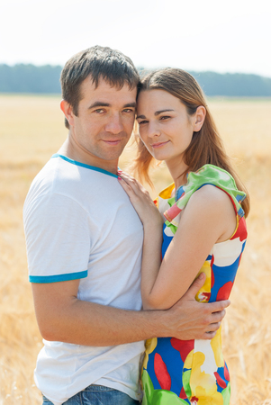 tenderly: Couple of lovers tenderly embrace in the field.