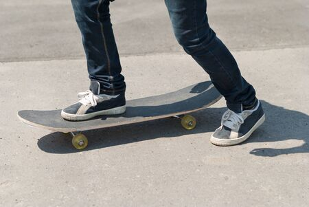 skateboard shoes: Skateboarder riding a skateboard on asphalt. Stock Photo
