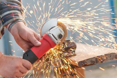 off cuts: Man cuts off a piece of metal.
