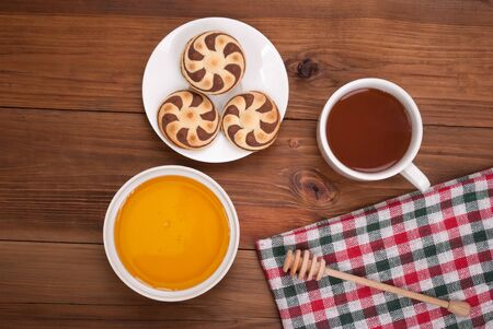 tea and biscuits: Cup of tea biscuits and honey on wooden background. Stock Photo