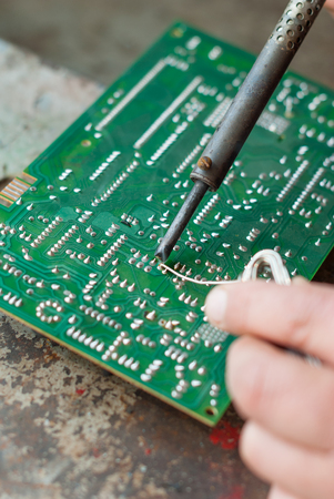 solder: Man with soldering iron to solder electronic board.